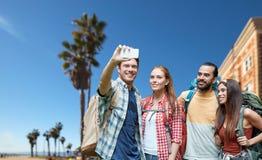 Freunde mit dem Rucksack, der selfie durch Smartphone nimmt lizenzfreies stockbild