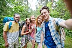 Freunde mit dem Rucksack, der selfie im Holz nimmt Stockfotografie