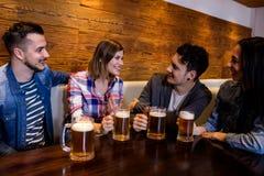 Freunde mit den Bierkrügen bei Tisch im Restaurant Lizenzfreie Stockbilder