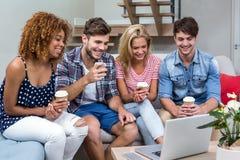 Freunde mit den Getränken, die im Laptop beim Sitzen auf Sofa schauen Stockfotos