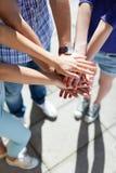 Freunde mit den Händen gestapelt im einstimmigen Lizenzfreie Stockfotos