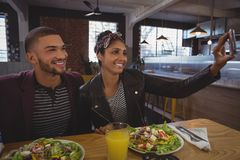 Freunde mit den Salatplatten, die selfie im Café nehmen Lizenzfreie Stockbilder