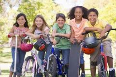 Freunde mit Fahrradrollern und -Skateboard Stockfotos