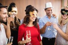 Freunde mit Masken auf dem Halten von Champagnergläsern Stockbild