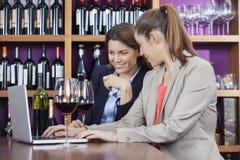 Freunde mit Rotwein-Gläsern unter Verwendung des Laptops bei Tisch Stockfotografie