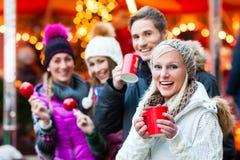 Freunde mit Süßigkeitsapfel und Eierpunsch auf Weihnachtsmarkt Stockbilder
