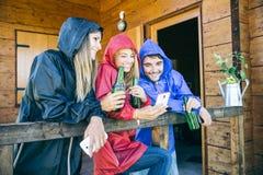 Freunde mit Smartphone an einem regnerischen Tag Lizenzfreies Stockbild