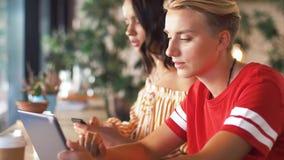 Freunde mit Tablette PC und Smartphone am Café stock footage