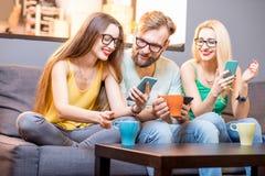 Freunde mit Telefonen zu Hause Stockfotografie