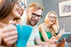 Freunde mit Telefonen zu Hause Stockfoto