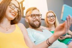 Freunde mit Telefonen zu Hause Lizenzfreie Stockfotos