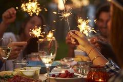 Freunde mit Wunderkerzen Lebensmittel essend und Partei genießend Lizenzfreie Stockfotos