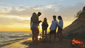 Freunde nähern sich Meer bei Sonnenuntergang stock footage