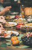 Freunde oder Familie, die am festlichen Weihnachtstisch essen lizenzfreies stockfoto