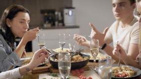 Freunde sitzen bei Tisch im Haus und genießen durch handgemachte Spaghettis mit Soße und plaudern nett stock video