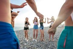 Freunde tanzen auf Strand unter Sonnenuntergangsonnenlicht und haben den Spaß, glücklich, genießen lizenzfreies stockbild