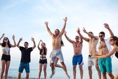 Freunde tanzen auf Strand unter Sonnenuntergangsonnenlicht und haben den Spaß, glücklich, genießen stockbild