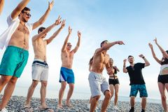 Freunde tanzen auf Strand unter Sonnenuntergangsonnenlicht und haben den Spaß, glücklich, genießen stockfoto