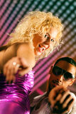 Freunde tanzen in Disco oder Club. Man and woman dancing to the music in a disco club having lots of fun Stock Photo