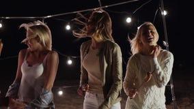 Freunde tanzt zusammen am Sand auf Nachtstrand auf Hintergrund des Dekors mit Lampen stock footage