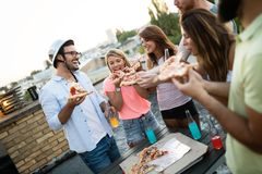 Freunde und Pizza Junge frohe Naturen, die Pizza essen und Spaß haben lizenzfreie stockfotografie