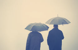 Freunde unter Regenschirme Stockfotos