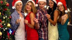 Freunde unter Weihnachtsbaum Leute mit Wunderkerze unter Weihnachtsbaum stock footage