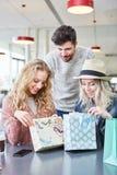 Freunde untersuchen neugierig ihre Einkaufstaschen lizenzfreie stockfotos
