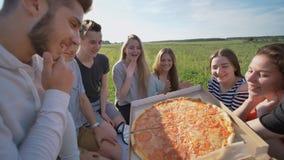 Freunde von Schulkindern essen Pizza draußen während des Sonnenuntergangs am Abend stockbild