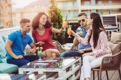 Freunde, welche die Cocktails im Freien auf einem Penthausbalkon trinken lizenzfreie stockfotos