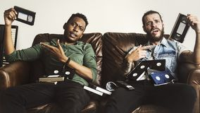 Freunde, welche die Videobänder sitzen auf Couch tragen Stockfotografie