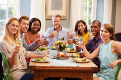 Freunde zu Hause, die um Tabelle für Abendessen sitzen stockfotografie