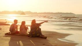 Freunde zwei junge Frauen und Mann sitzen auf tropischem Küstenstrand bei Sonnenuntergang und betrachten Wasser Sommerreise, Feri stockbilder