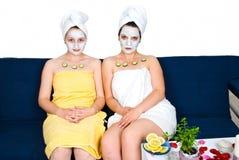 Freundfrauen mit Gesichtsschablone an der Badekurortrücksortierung Lizenzfreies Stockfoto