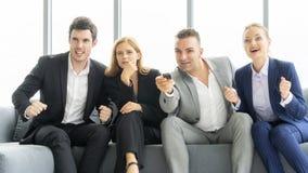 Freundgeschäftssitzen auf der Couch, die an Fernsehprogramm aufregt professionelles glückliches Lebenkonzept der Teamwork lizenzfreie stockbilder