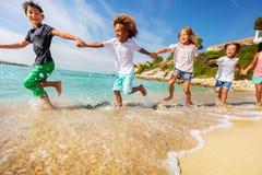 Freundhändchenhalten und -betrieb entlang dem Strand lizenzfreies stockfoto