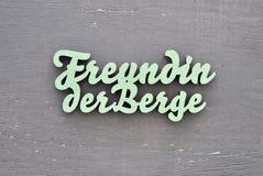 Freundin der Berge Schriftzug grün. Laser Typographic Cut Freundin der Berge, green with grey background, text in german stock photography