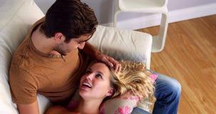 Freundin, die auf dem Schoss ihres Freundes auf der Couch liegt stock video footage