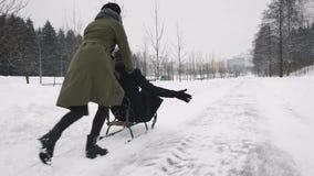 Freundin, die ihren Freund auf einem Pferdeschlitten zieht stock video