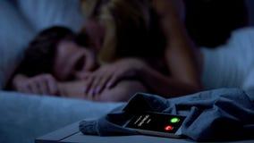 Freundin, die während Geliebte kommt und küsst schläfrigen Mann, Verrat nennt stockfoto