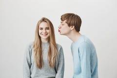 Freundin neckt Freund, der irgendeinen Kuss wünscht Lustiger reizend Kerl, verbiegend in Richtung zum Mädchen mit den gefalteten  lizenzfreie stockfotos