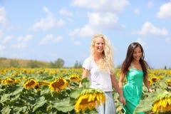 Freundinhändchenhalten im Sonnenblumenfeld Stockbilder