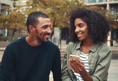 Freundinholdinghandy in der Hand, der ihren Freund betrachtet lizenzfreies stockbild