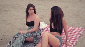 Freundinnen, die auf dem Strand und der Unterhaltung sitzen stock footage