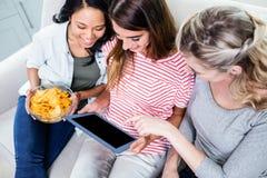 Freundinnen, die in der digitalen Tablette beim Essen von Snäcken schauen Lizenzfreie Stockbilder