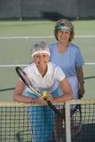 Freundinnen, die Doppelte am Tennisplatz spielen lizenzfreie stockfotos