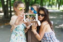 Freundinnen, die draußen Fotos mit Smartphone machen Stockbilder