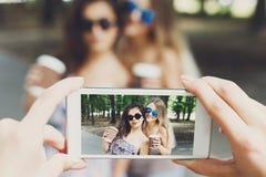 Freundinnen, die draußen Fotos mit Smartphone machen Stockfotos