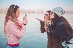 Freundinnen, die ein Foto von ihnen Kuss sendend machen Stockbilder
