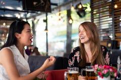 Freundinnen, die ein Gespräch in einem Restaurant haben lizenzfreies stockbild